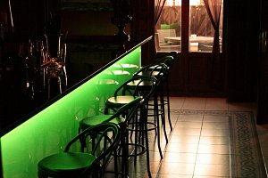 A bar with green chairs