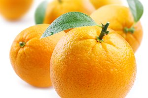 ripe oranges with leaves on white background
