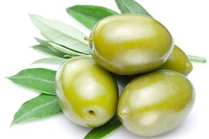 Green olives with leaves on a white.