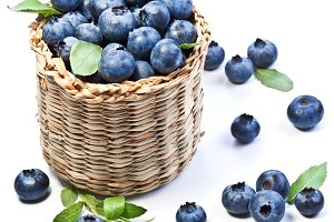 Blueberries in a basket on a white background.