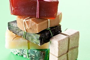 Pieces of different natural soap on a green background.