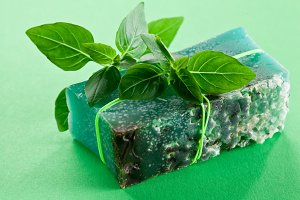 Piece of natural soap with basil on a green background.