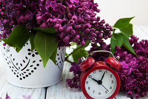 Lilac flowers and alarm clock