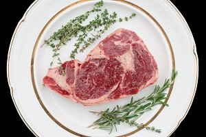 Raw rib-eye steak with herbs