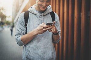 Cheerful guy using smartphone