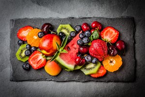 Assortment summer fresh berries and fruits on black slate plate