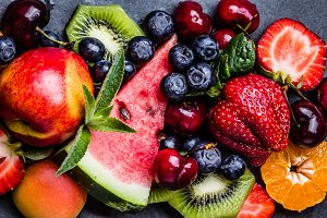 Assortment summer fresh berries and fruits on black slate plate