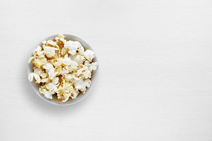 Popcorn in bowl on white table