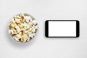 Popcorn and smartphone on table