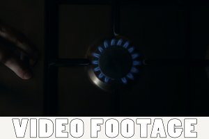 A man lights a gas stove top