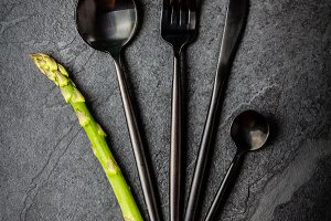 Set of cutlery and asparagus on black stone slate background.
