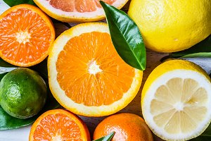 Assorted fresh citrus fruits with leaves. Background