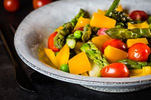 Vegetarian salad with asparagus, cherry tomatoes, bell pepper, slate background