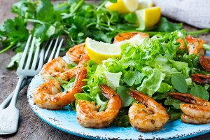 Seafood shrimp lettuce salad on blue plate