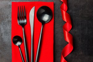Menu background. Steel black cutlery set on red napkin