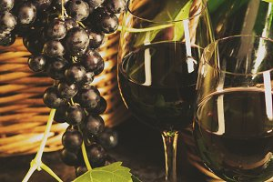 Two glasses of red wine and grapes with leaves