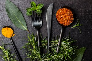 Food black background with herbs, spices and cutlery. top view