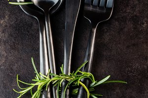 Set of cutlery knife, spoon, fork, rosemary. Black background.