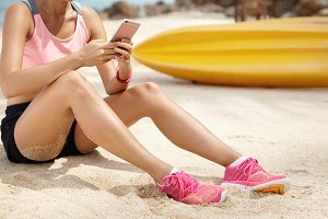 Sports, technology and leisure concept. Cropped shot of young athletic woman with fit beautiful legs in pink running shoes sitting on sandy beach using cell phone while relaxing after jogging workout