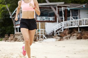 Motivation, determination and endurance. Cardio running workout. Unrecognizable woman runner in motion wearing pink top and black shorts jogging on beach on sunny day with bungalow on background