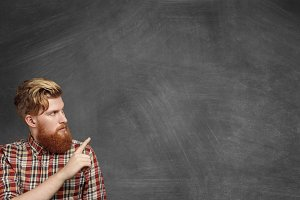 Advertising concept. Handsome young bearded man in casual checkered shirt looking at blank blackboard and pointing his index finger at copy space for your text or promotional content. Horizontal
