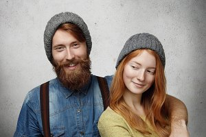 Isolated shot of beautiful happy couple wearing warm gray knitted hats in studio. Cheerful man with trendy fuzzy beard embracing his attractive redhead girlfriend who is looking with cute sly smile