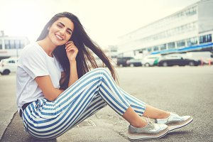 Woman in striped pants and running shoes smiles