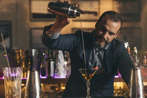 Expert barman is making cocktail.