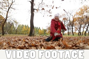 Girl plays with autumn fallen leaves