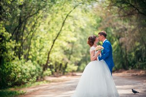 young bride and groom embracing against the backdrop of the forest the road