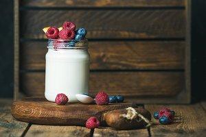 Glass jar of yogurt with berries