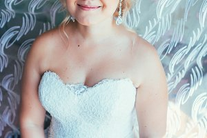 portrait of young beautiful happy bride near the window