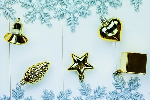 Seasonal Christmas ornaments and snowflakes on white wood background