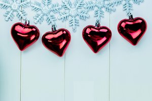 Snowflakes and heart ornaments hanging on white wood background