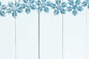 Light blue snowflakes decorated on white wood background - with copyspace