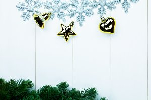 Part of spruce Christmas tree and golden ornaments and snowflakes on white wood background