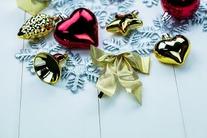 Seasonal Christmas ornaments and snowflakes on white wood background - Close-up