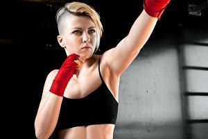 Cool sport girl in red boxing bandages punches