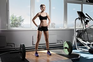 young woman standing at gym with barbells on floor