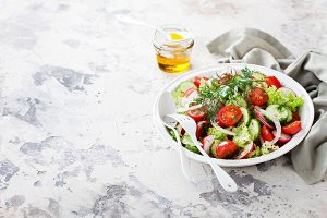 Fresh salad with cherry tomatoes, cucumbers, radishes, dill and olive oil