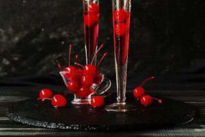 Fruit liqueur or apirol with cherries cocktail on black background