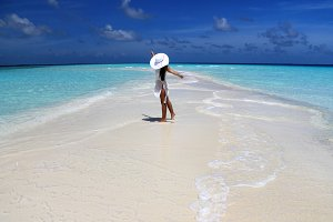 Girl dances at sandbank, Maldives