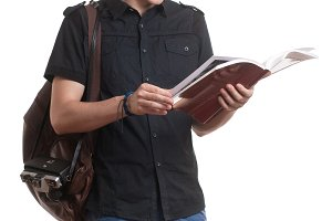 young man standing reading book bag