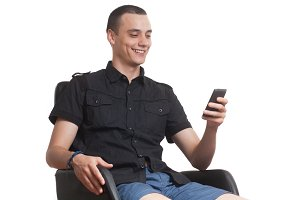young man using phone sitting, white