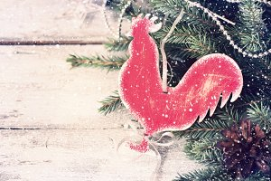 New Year's vintage background with a homemade toy Rooster. Tinte