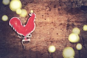 Vintage background with a homemade toy Rooster. Vintage symbol o