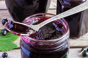 Black currant jam on a wooden background