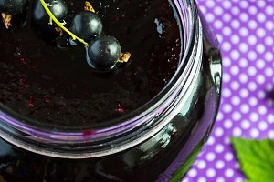 Black currant jam in a glass jar, selective focus