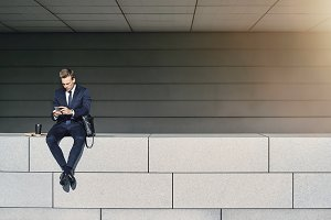 Male in suit sitting and using phone