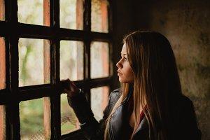 Pensive blonde girl next a windows